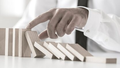 businessman stopping domino